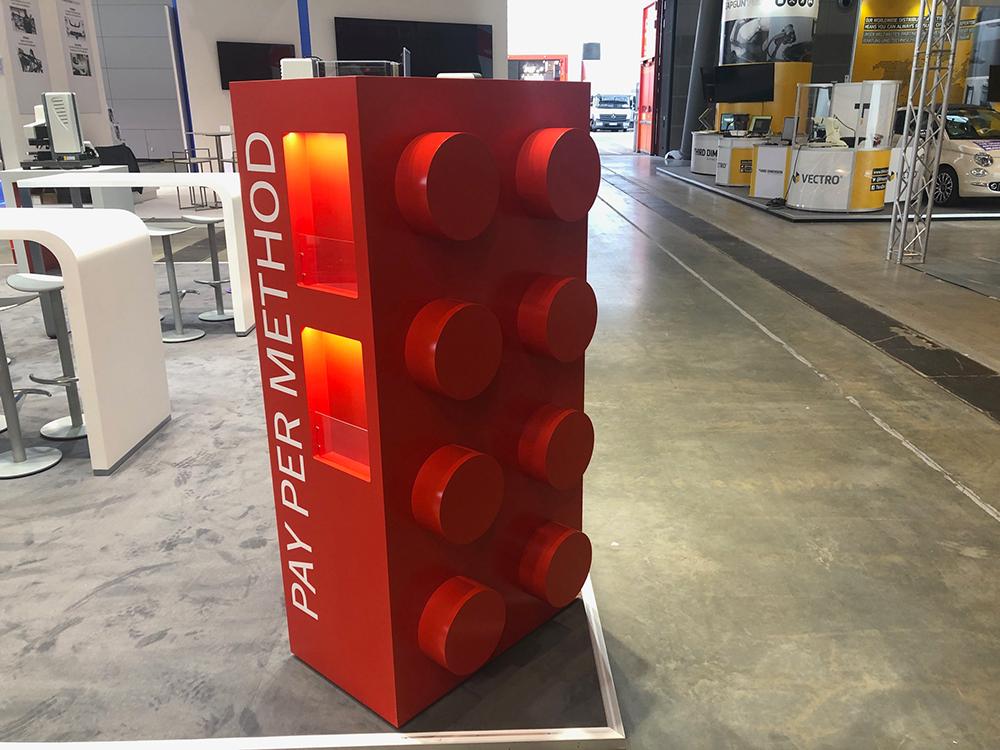 Großer Nachbau eines Lego Steines als Wandschrank mit Prospektnieschen auf der Control in Stuttgart 2019