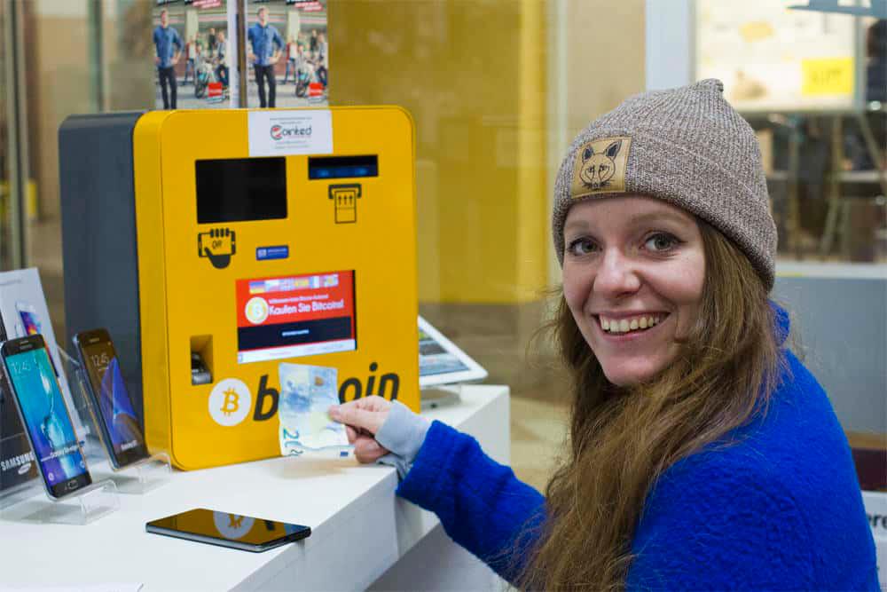 Junge Frau wechselt 20 Euro am Bitcoin Automaten ATM in Bitcoin oder andere Krypto Währungen